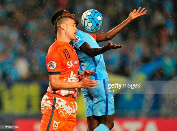 Ramires Santos of Jiangsu FC fights for the ball with Marcelo Toscano of Jeju United FC during their AFC Champions League group stage football match...