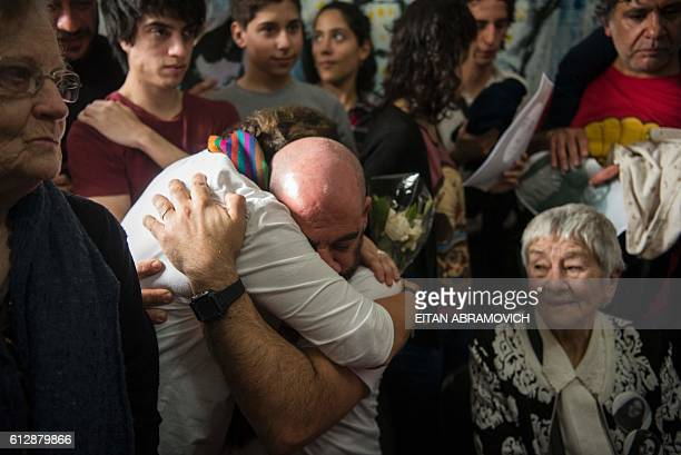 Ramiro Menna brother of the 121st grandson found by the Abuelas of the Plaza de Mayo humanitarian organization is greeted by a relative as he sits...