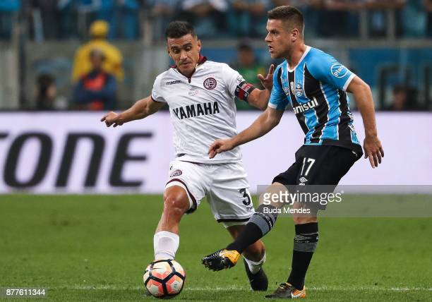 Ramiro of Gremio struggles for the ball with Maximiliano Velazquez of Lanus during a first leg match between Gremio and Lanus as part of Copa...