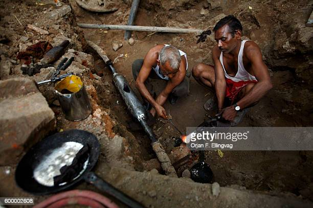 Ramjeelal and his colleague work to repair a broken electrical line cut by workers repairing another cable as the demand for comfort and luxury...