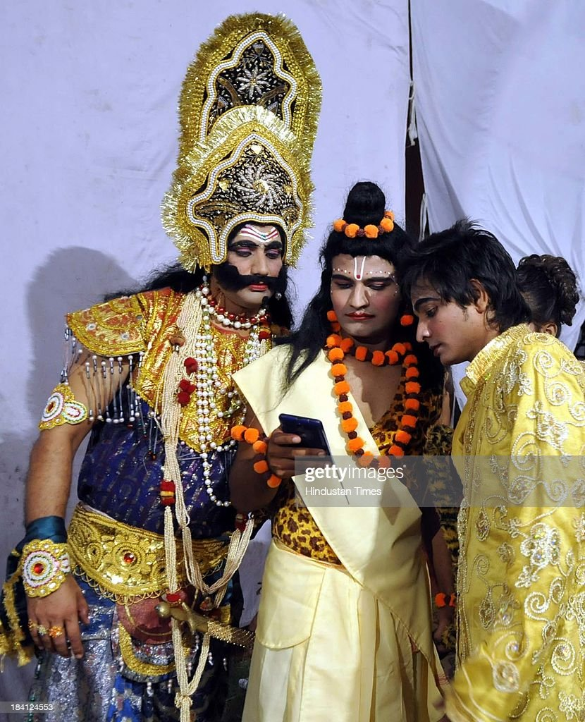 Ramlila actors checking their pictures on mobile in backstage of Ramleela at Noida stadium on October 11 2013 in Noida India Ramlila is a dramatic...