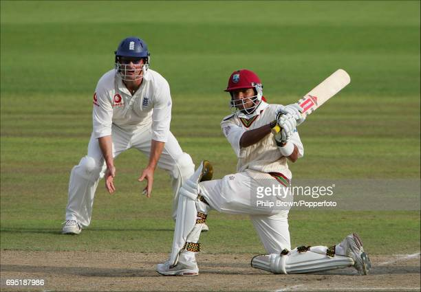 Ramnaresh Sarwan of the West Indies hits a four off Ashley Giles of England as Andrew Strauss of England looks on during the 3rd Test Match between...