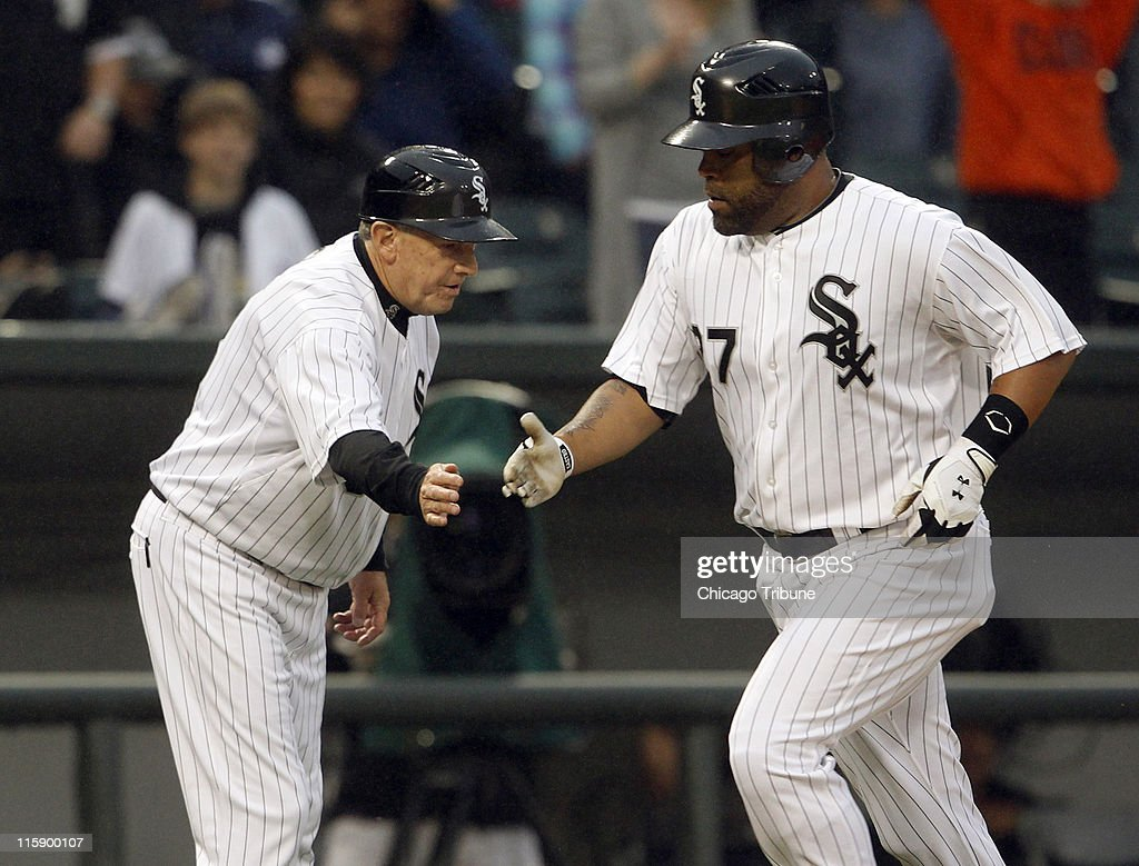 Ramon Castro, right, of the Chicago White Sox is congratulated by third base coach Jeff Cox after his solo home run against the Oakland Athletics during the forth inning at U.S. Cellular Field in Chicago, Illinois, on Saturday, June 11, 2011.