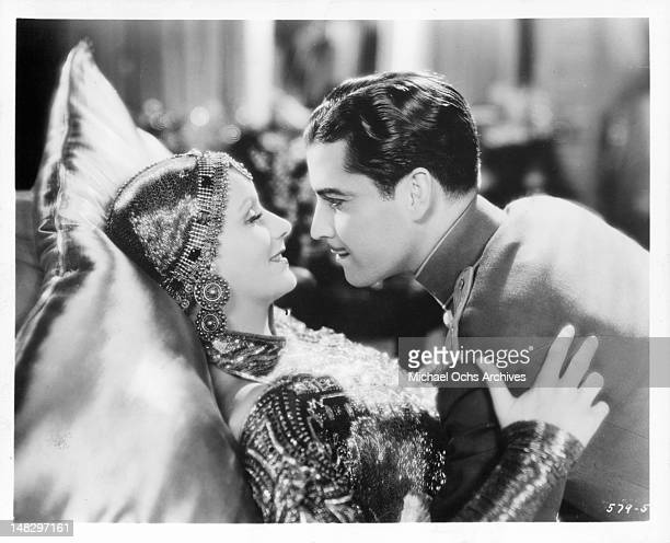 Ramon Novarro moving closer to kiss Greta Garbo as she rests her head on a large satin pillow in a scene from the film 'Mata Hari' 1931