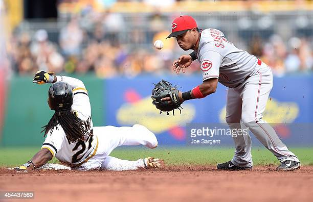 Ramon Santiago of the Cincinnati Reds can't turn a double play in front of Andrew McCutchen of the Pittsburgh Pirates during the sixth inning on...