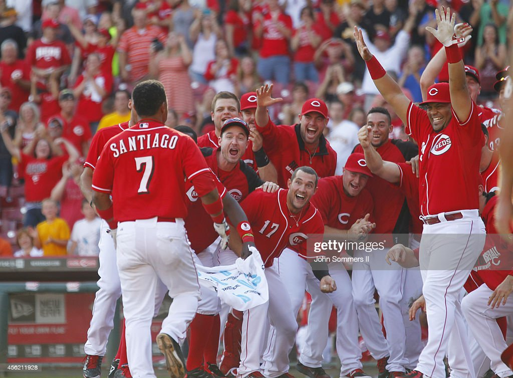Ramon Santiago #7 of the Cincinnati Reds celebrates his walk off grand slam home run with teammates in the 10th inning of play against the Pittsburgh Pirates at Great American Ball Park on September 27, 2014 in Cincinnati, Ohio.