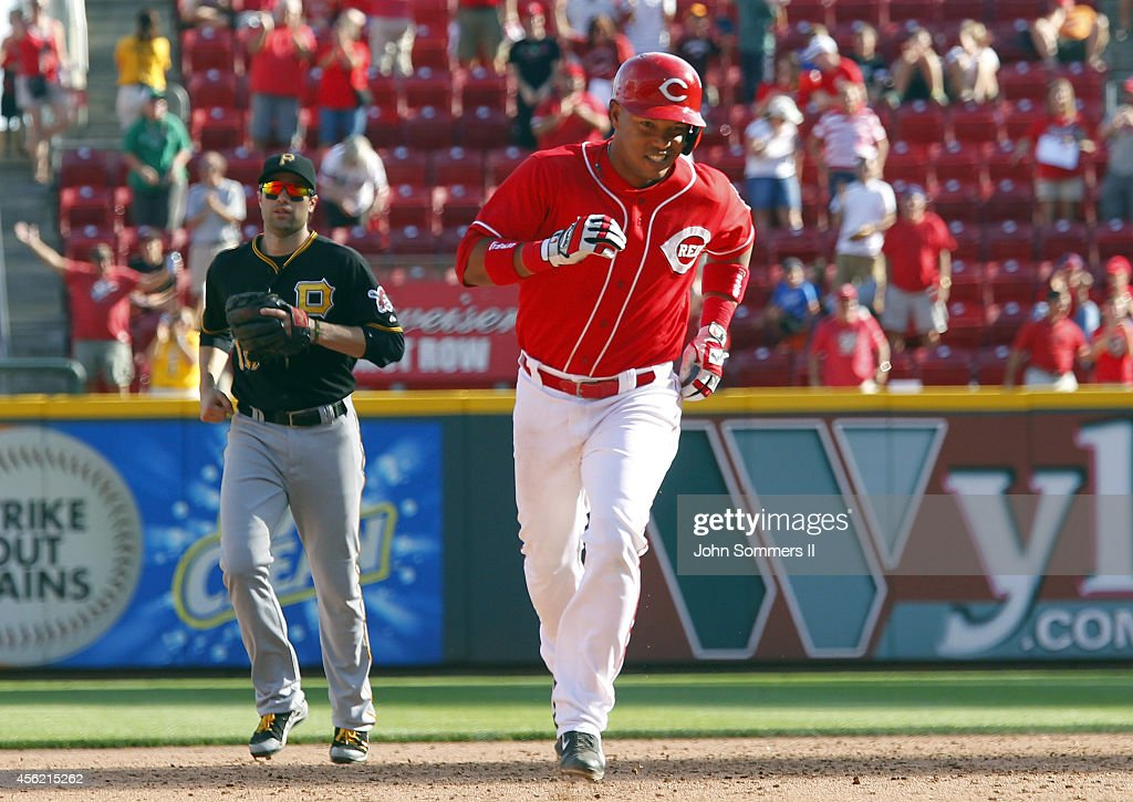 Ramon Santiago #7 of the Cincinnati Reds celebrates his walk-off grand slam home run as he rounds the bases in the 10th inning of play against the Pittsburgh Pirates at Great American Ball Park on September 27, 2014 in Cincinnati, Ohio.