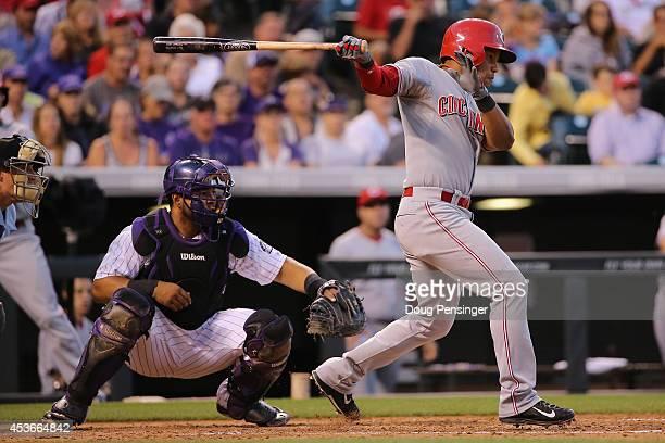 Ramon Santiago of the Cincinnati Reds hits an RBI single off of Nick Masset of the Colorado Rockies to score Jack Hannahan of the Cincinnati Reds and...