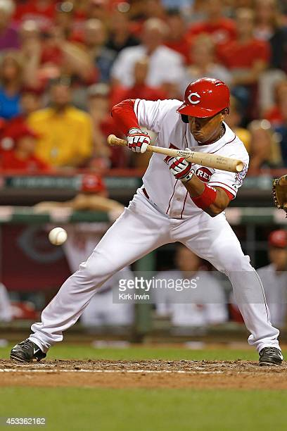 Ramon Santiago of the Cincinnati Reds lays down a sacrifice bunt during the eighth inning against the Miami Marlins at Great American Ball Park on...