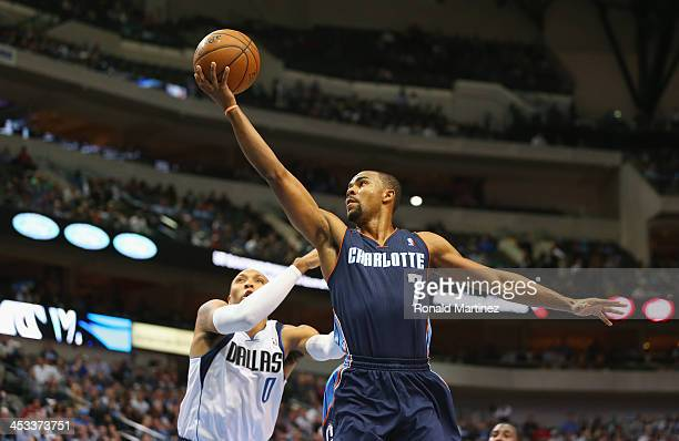Ramon Sessions of the Charlotte Bobcats takes a shot against Shawn Marion of the Dallas Mavericks at American Airlines Center on December 3 2013 in...