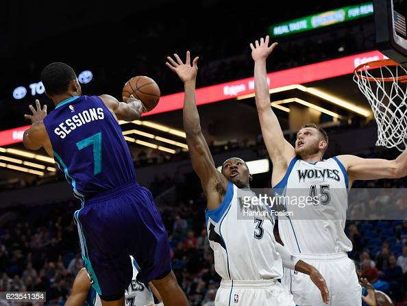 Ramon Sessions of the Charlotte Hornets passes the ball past Kris Dunn and Cole Aldrich of the Minnesota Timberwolves during the fourth quarter of...