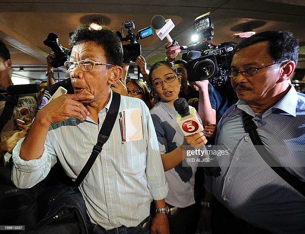 Ramon Tertosa (R) and Crisostomo Carabio (L), Filipino labourers working at the time when Islamists siezed workers at a gas plant in Algeria, but were not taken hostage, are mobbed by members of the media shortly after arriving at the international airport in Manila on January 23, 2013. Islamic militants used foreign hostages as human shields to stop Algerian troops aboard helicopters from strafing them with gunfire, Filipino survivor Joseph Balmaceda of the four-day bloodbath recounted January 21.