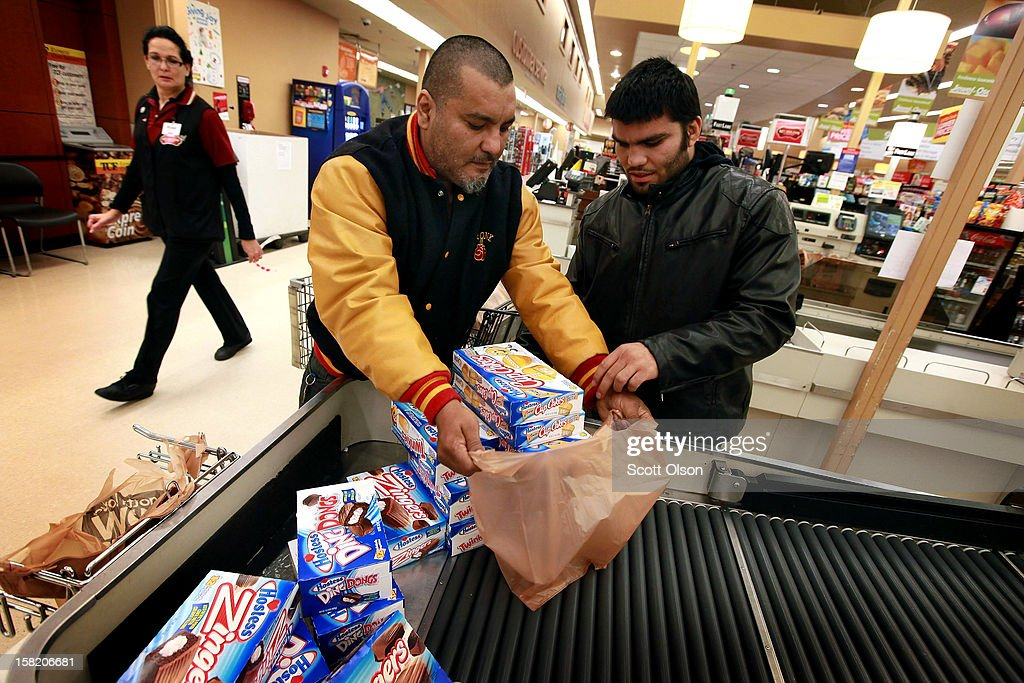 Ramon Valenzuela Sr. (L) and Ramon Valenzuela Jr. bag their purchase of Hostess snacks at a Jewel-Osco grocery store on December 11, 2012 in Chicago, Illinois. The Jewel-Osco grocery store chain purchased the last shipment of 20,000 boxes of Hostess products and put them on sale in their stores throughout the Chicago area today. Hostess Brands Inc. shut down its baking operations and began liquidating assets last month after failing to negotiate a labor contract with Workers with the Bakery, Confectionery, Tobacco Workers and Grain Millers International Union