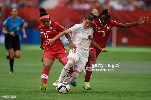 Ramona Bachmann of Switzerland is sandwiched by Desiree Scott and Kadeisha Buchanan of Canada during the FIFA Women's World Cup 2015 Round of 16...