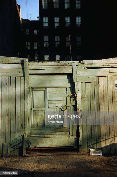A ramshackle doorway amidst US tenement blocks circa 1970