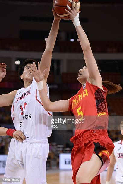 Ramu Tokashiki of Japan and Xiaoxia Chen of China compete for the ball in finals match between Japan and China during the 2015 FIBA Asia Championship...
