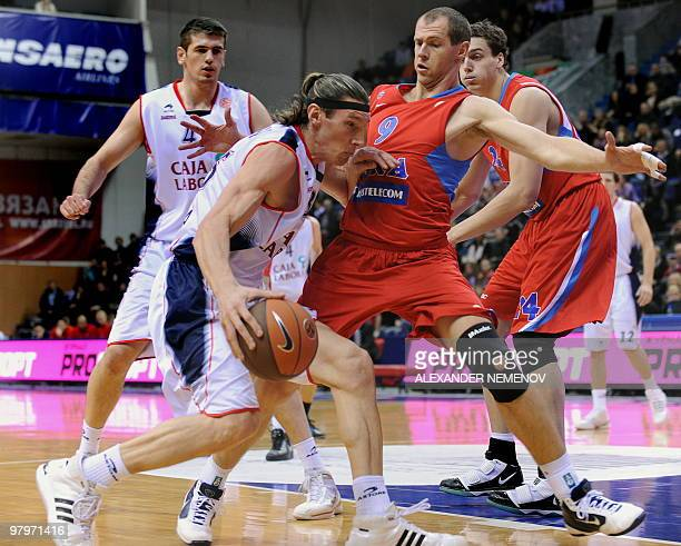 Ramunas Siskauskas of CSKA fights for the ball with Walter Herrmann of Caja Laboral in Moscow on 23 March 2010 during their Euroleague quarterfinal...