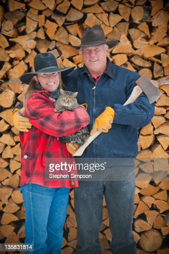 ranch couple portrait with cat and firewood : Stock Photo