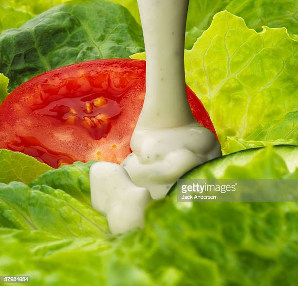 Ranch dressing pouring on salad