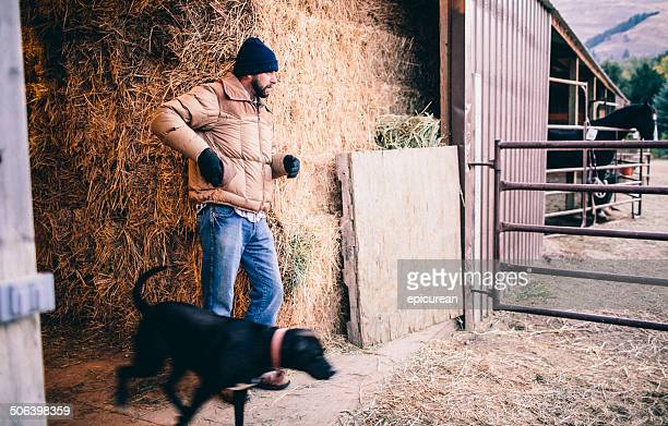 Ranch working man walks out of hay barn with dog