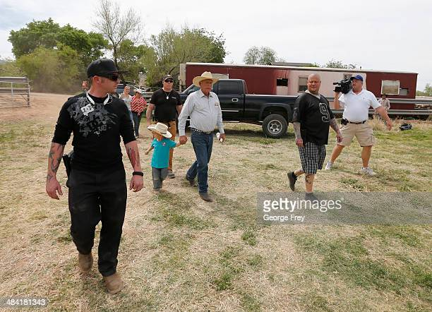 Rancher Cliven Bundy with his grandson Braxton Louge in tow and armed security guards leave his ranch house on April 11 2014 west of Mesquite Nevada...