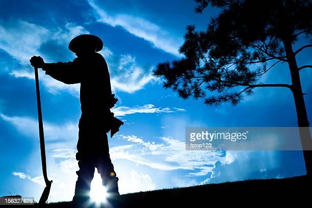 Ganadero agricultor con vista al campo después de la tormenta de lluvia. Puesta de sol. Silhouette. Sky.