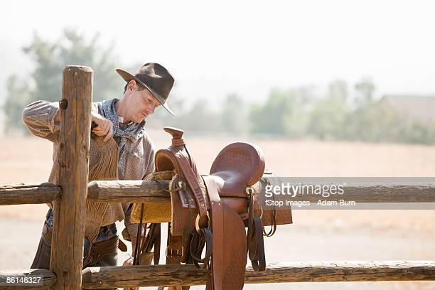 A rancher preparing a horse saddle on a fence