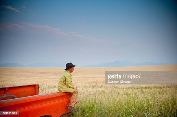 rancher sitting on old pickup truck, sunset