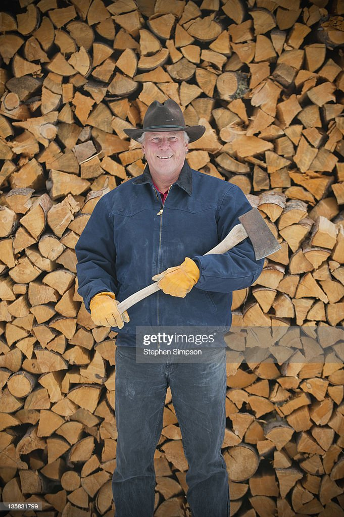 rancher with pile of split and stacked firewood : Stock Photo