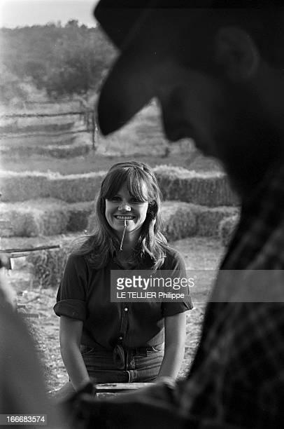 Ranches For Tourism And Recreation In France En France le 20 juin 1966 portrait d'une jeune femme avec une brindille d'herbe à la bouche souriante...