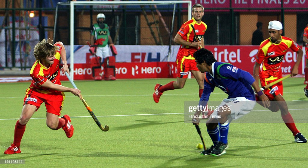 Ranchi Rhinos (red jersey) and Uttar Pradesh Wizard (Blue jersey) team sin action during the Hockey India League (HIL) semi final match at Astro turf stadium on February 9, 2013 in Ranchi, India.