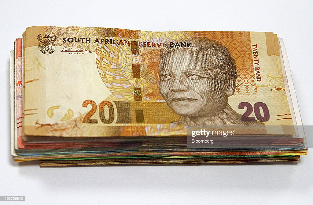 A 20 rand currency banknote sits on top of a bundle of mixed denomination notes in this arranged photograph at a First National Bank (FNB) branch in Johannesburg, South Africa, on Friday, March 15, 2013. A recovery in mining and manufacturing is giving South Africa's rand and bonds a breather amid concern that growth is slowing while inflation accelerates. Photographer: Nadine Hutton/Bloomberg via Getty Images