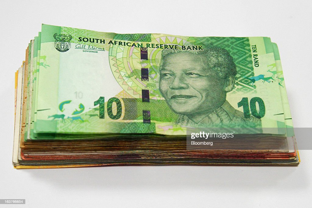 A 10 rand currency banknote sits on top of a bundle of mixed denomination notes in this arranged photograph at a First National Bank (FNB) branch in Johannesburg, South Africa, on Friday, March 15, 2013. A recovery in mining and manufacturing is giving South Africa's rand and bonds a breather amid concern that growth is slowing while inflation accelerates. Photographer: Nadine Hutton/Bloomberg via Getty Images