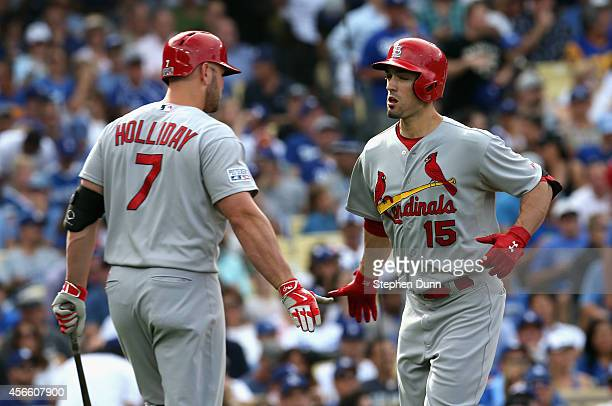 Randal Grichuk of the St Louis Cardinals celebrates with teammate Matt Holliday after hitting a homerun to score in the first inning of Game One of...