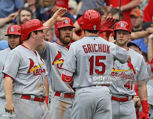 Randal Grichuk of the St Louis Cardinals is greeted by Jedd Gyorko Brandon Moss and Jeremy Hazelbaker after hitting a grand slam home run in the 8th...