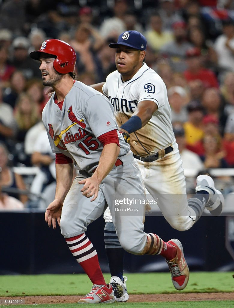 Randal Grichuk #15 of the St. Louis Cardinals is tagged out in a run down by Yangervis Solarte #26 of the San Diego Padres during the fourth inning of a baseball game at PETCO Park on September 5, 2017 in San Diego, California.