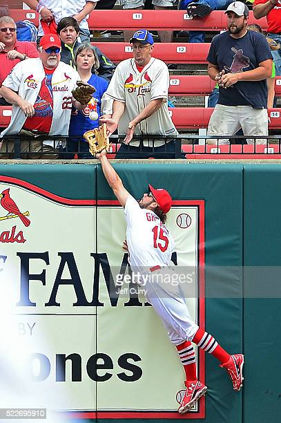 Randal Grichuk of the St Louis Cardinals leaps and robs Anthony Rizzo of the Chicago Cubs of a home run during the first inning at Busch Stadium on...