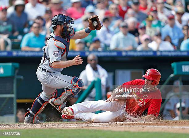 Randal Grichuk scores the winning run on a single by Pete Kozma of the St Louis Cardinals under the attempted tag of Bryan Holaday of the Detroit...