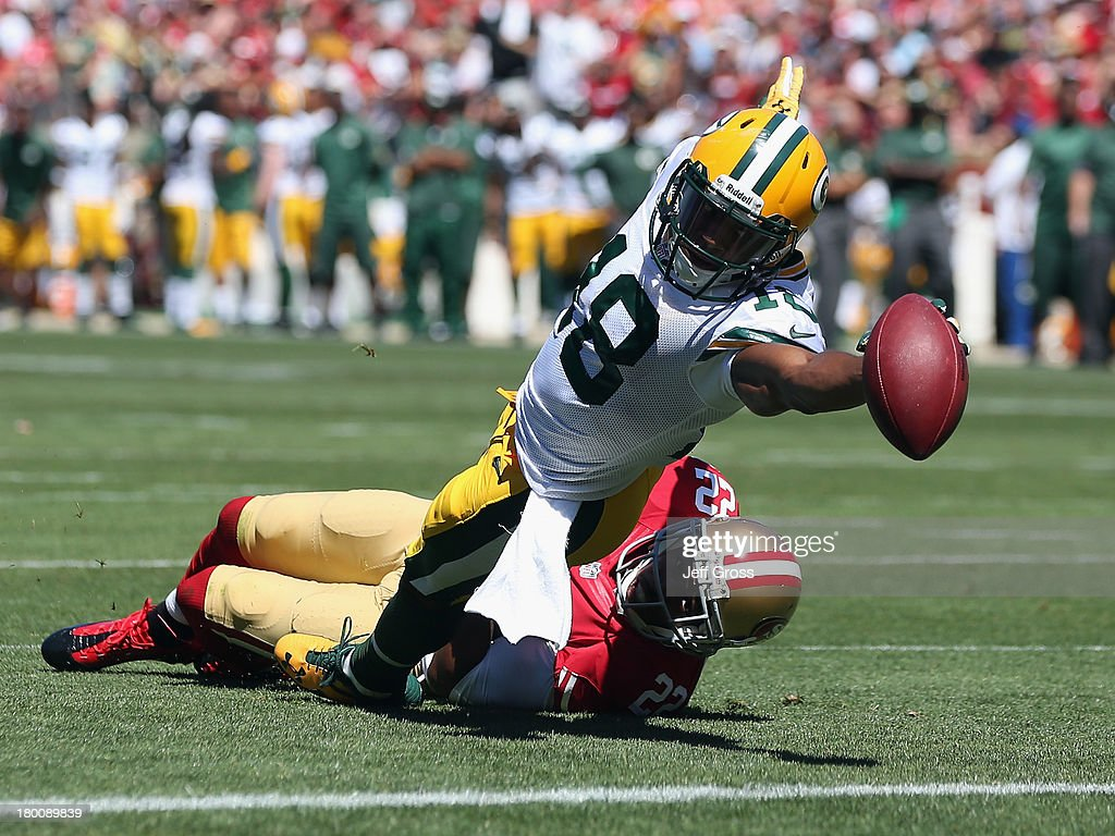 Randall Cobb #18 of the Green Bay Packers stretches across the goal line for a touchdown while being pulled down by Carlos Rogers #22 of the San Francisco 49ers in the first quarter at Candlestick Park on September 8, 2013 in San Francisco, California. The 49ers defeated the Packers 34-28.