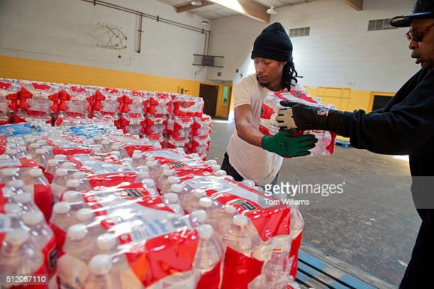 Randall Hopskon Jr left and Bennie Thornton stock bottled water in the basement of the St Mark Baptist Church in Flint Mich February 23 2016 The...
