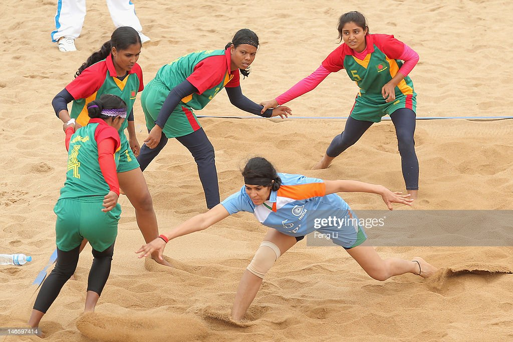 Randeep Kaur Khehra (Front) of India is tackled as she competes during the Beach Kabaddi Women's Team Group A match between India and Bangladesh on Day 4 of the 3rd Asian Beach Games Haiyang 2012 at Fengxiang Beach on June 20, 2012 in Haiyang, China.