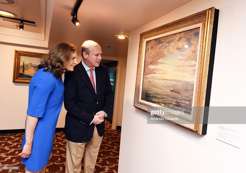 Randolph Churchill (R) and his wife Catherine Churchill open an exhibition of Winston Churchill's paintings to coincide with the 80th anniversary celebration of the Queen Mary's maiden voyage at The Queen Mary on May 27, 2016 in Long Beach, California. All paintings are copyright of the Churchill Heritage Limited.