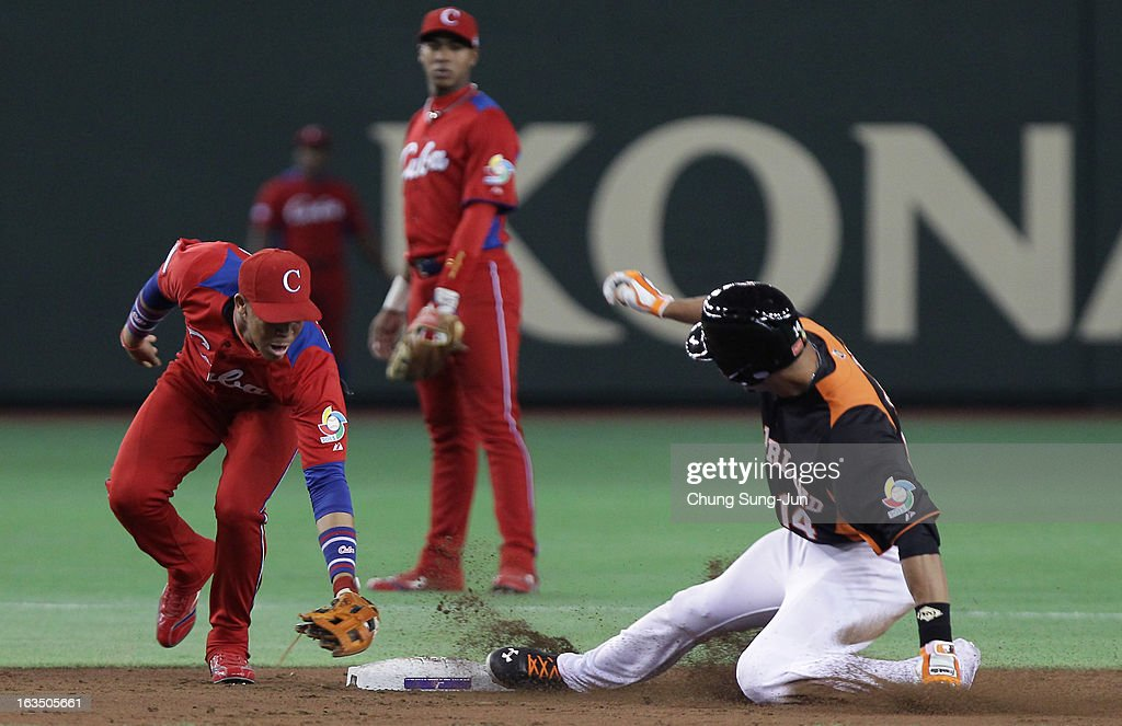 Randolph Oduber # 14 of Netherlands slides safely into second base as Jose Fernandez # 8 of Cuba tags in the third inning during the World Baseball Classic Second Round Pool 1 game between Cuba and the Netherlands at Tokyo Dome on March 11, 2013 in Tokyo, Japan.