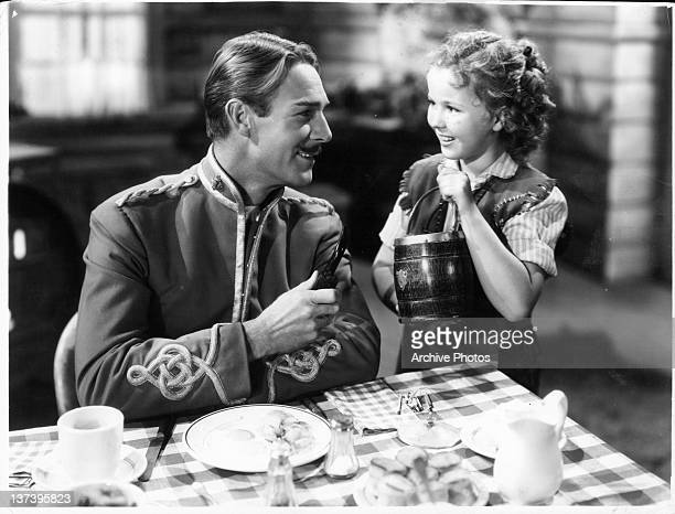 Randolph Scott smiling at Shirley Temple in a scene from the film 'Susannah Of The Mounties' 1939