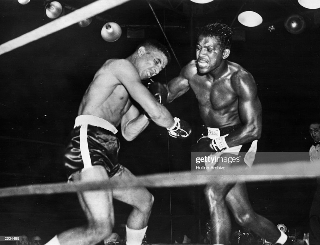 Randolph Turpin buckles under a blow from Sugar Ray Robinson during their world middleweight title fight at the Polo Ground in New York