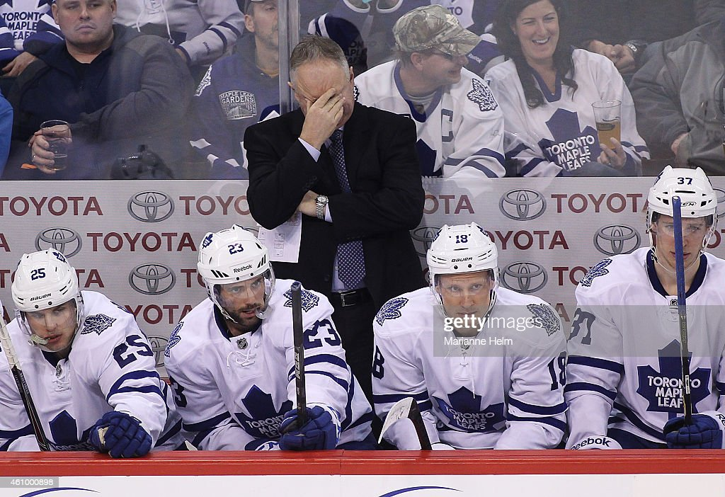 Randy Carlyle, head coach of the Toronto Maple Leafs, rubs his eyes on the bench in third period action in an NHL game against the Winnipeg Jets at the MTS Centre on January 3, 2015 in Winnipeg, Manitoba, Canada.