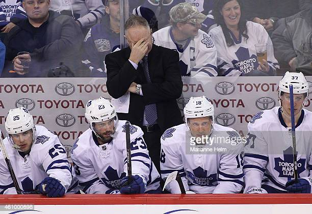 Randy Carlyle head coach of the Toronto Maple Leafs rubs his eyes on the bench in third period action in an NHL game against the Winnipeg Jets at the...
