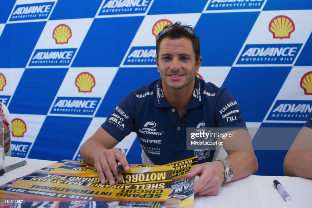 Randy De Puniet of France and Suzuki Test Team signs autographs for fans during the autographs session during the MotoGP Of Malaysia Qualifying at...