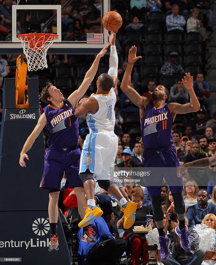 Randy Foye #4 of the Denver Nuggets lays up a shot between Goran Dragic #1 of the Phoenix Suns and Markieff Morris #11 of the Phoenix Suns during preseason action at Pepsi Center on October 23, 2013 in Denver, Colorado. The Suns defeated the Nuggets 98-79.