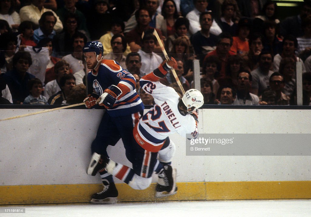 Randy Gregg #21 of the Edmonton Oilers is checked by John Tonelli #27 of the New York Islanders during the 1984 Stanley Cup Finals in May, 1984 at the Nassau Coliseum in Uniondale, New York.